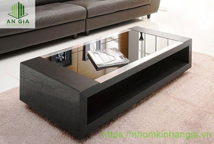 Mẫu 11: Khác với những kiểu bàn kính phòng khách đã được nêu ở trên, mẫu bàn này có cấu trúc chính từ gỗ phần mặt bàn có diện tích nhỏ từ kính cường lực đen