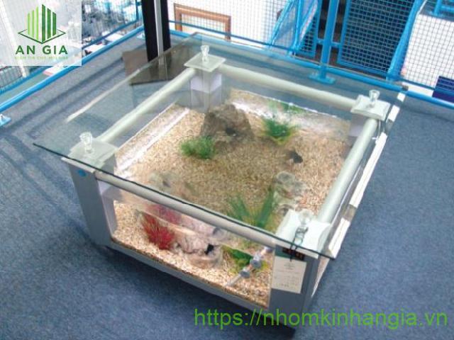 Mẫu 3: Vẫn là thiết kế dạng hình khối vuông đặc trưng của mẫu bàn kính bể cá thông dụng nhưng phần khung bê tông đã tạo nên điểm khác biệt cho sản phẩm
